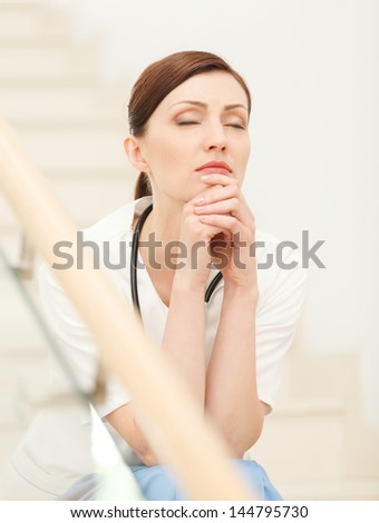 Tired and depressed. Beautiful young female doctor sitting at the staircase with her eyes closed and holding her hands on chin