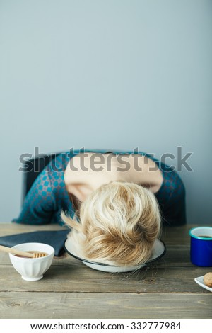 tired and exhausted lady puts her head into her plate
