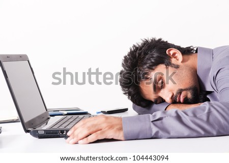 tired and fatigued businessman sleeping on the desk - stock photo