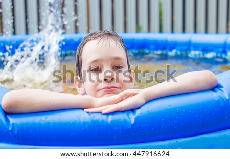 tired and happy child on the edge of pool. boy takes a break from swimming in inflatable pool - stock photo