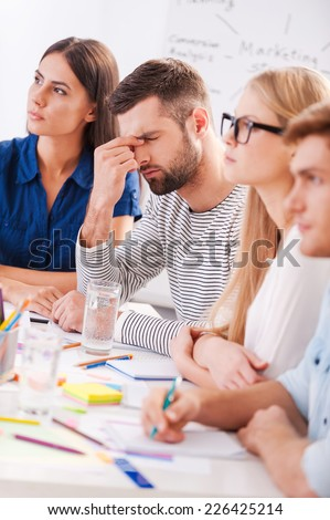 Tired and stressed. Depressed young man touching face with hand while sitting at the table together with his colleagues  - stock photo