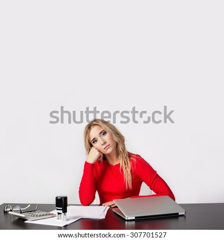 Tired and Thinking Young Business Woman at the desk with laptop and papers. Dream about Relax and Holiday, Vacation planning