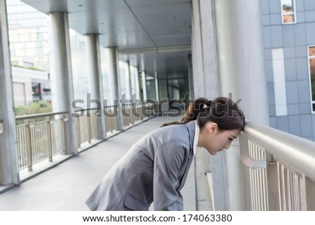 Tired Asian business woman put head on balustrade in modern city. - stock photo