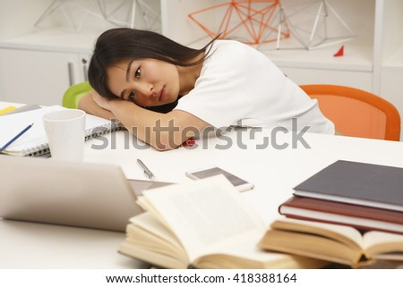 Tired Asian student resting after hard-working day in library. Exhausted woman lying on table with her eyes opened.