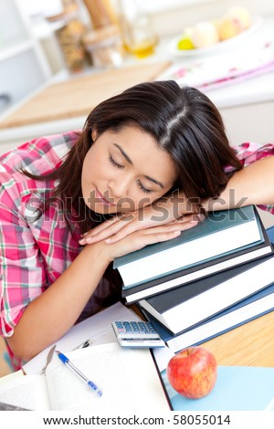 Tired asian student sleeping on her books in the kitchen - stock photo