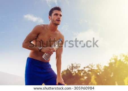 Tired athlete resting with bottle of water