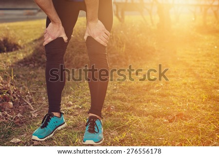 Tired athlete standing in park at sunset and resting (intentional sun glare) - stock photo