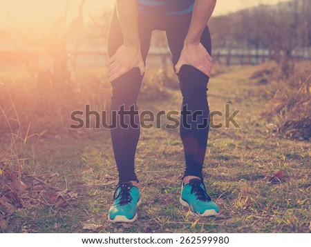 Tired athlete standing in park at sunset and resting (intentional sun glare and vintage color)