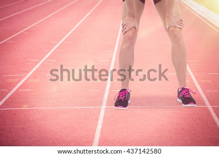 Tired athlete standing with hand on knee against focus of athletics track