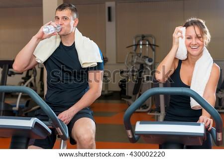 tired athletes on exercise bikes take a break - stock photo
