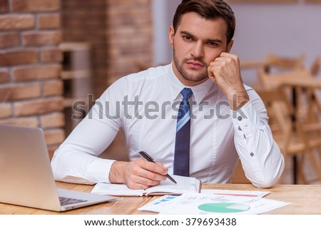 Tired attractive young businessman in white classical shirt using a laptop and making notes while working in the cafe
