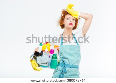 Tired attractive young woman in yellow gloves and blue apron standing and holding box with detergents over white background - stock photo