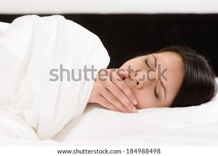 Tired attractive young woman lying in bed yawning with her hand to her mouth and eyes closed as she prepares to go into a refreshing sleep to ease her fatigue - stock photo