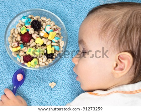 Tired Baby sleeping beside full bowl of cereal