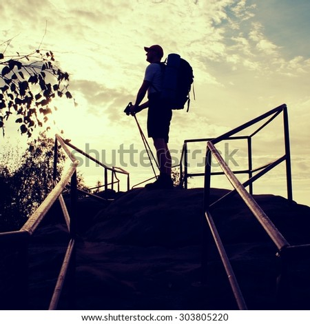 Tired  backpacker with poles. Sunny spring daybreak in rocky mountains. Hiker with big backpack, baseball cap, dark pants and white shirt.  - stock photo