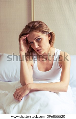 Tired beautiful girl leaning on her hand and looking at camera, sitting in bed