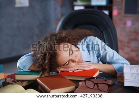 Tired beautiful girl sleeping on table - stock photo