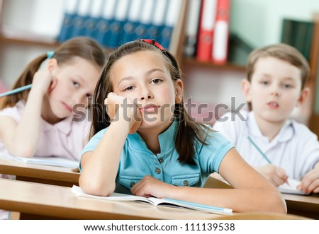 Tired beautiful schoolgirl dreams at the school desk and leans on her hand - stock photo