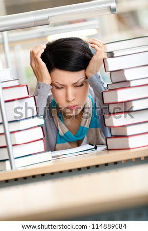 Tired beautiful woman with headache sitting at the desk surrounded with piles of books - stock photo