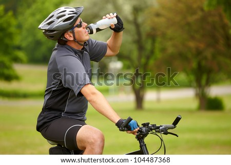 Tired biker resting and drinking from water bottle.