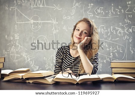 Tired blonde student on her desk with many books