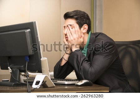 Tired bored young businessman sitting at his desk in front of his computer with his chin resting on his hands and eyes closed - stock photo