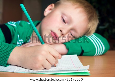Tired boring boy doing his difficult school homework - stock photo