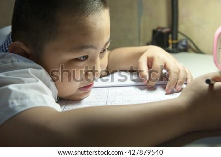 Tired boring boy doing his difficult school homework - stock photo