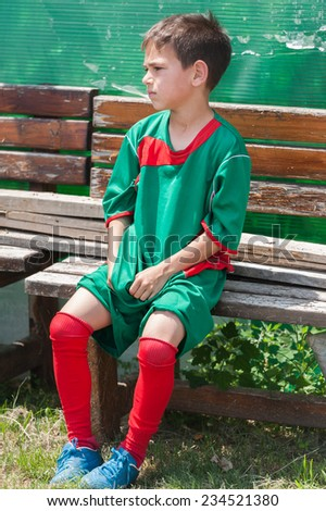 Tired boy after soccer matches - stock photo