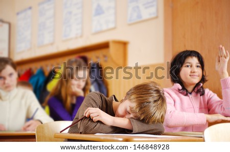 Tired boy is sleeping during school lesson - stock photo