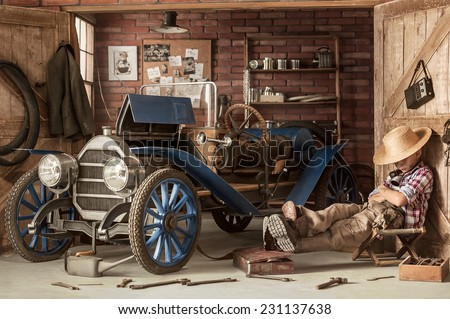 Tired boy mechanic resting in the retro car in the garage of a summer sunny day - stock photo