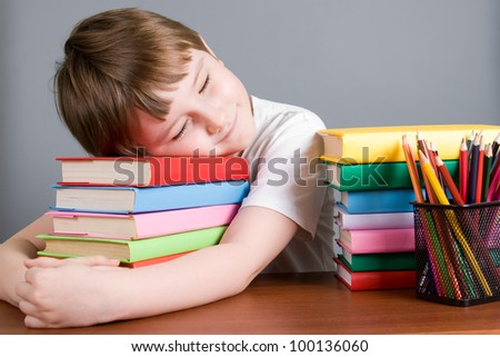 Tired boy sleeps on the books on a gray background - stock photo