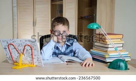 Tired Boy Wearing Funny Glasses Doing Homework. Child With Learning Difficulties. Boy Having Problems With His Homework. Education Concept. - stock photo