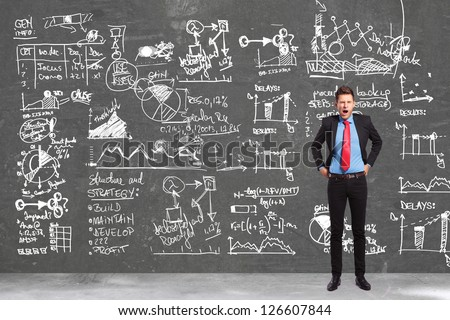 tired business man yawning in front of a big business plan - stock photo
