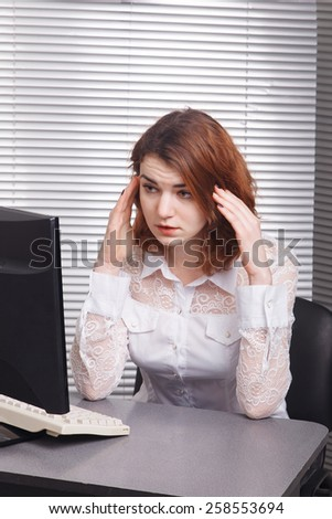 Tired business woman looks tired in the computer