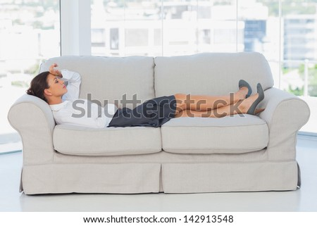 Tired business woman lying down on the couch - stock photo