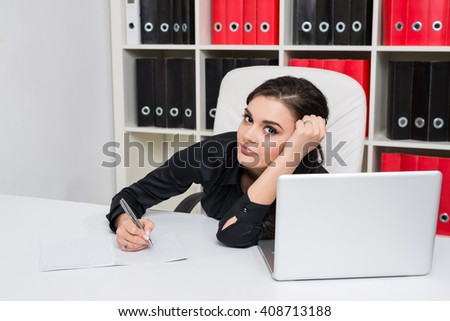 Tired business woman props her head by hand and take notes in a notebook, in the background bookcase with folders for papers - stock photo