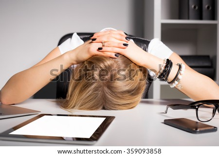 Tired business woman resting her head on desk  - stock photo