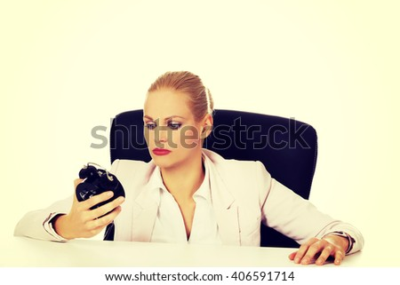 Tired business woman sitting behind the desk and holding alarm clock - stock photo