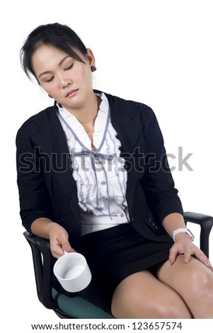 Tired business woman sleeping in her chair and holding empty coffee cup. Isoleted on white background. Model is Asian woman. - stock photo