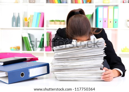 Tired business woman with documents in her workplace - stock photo