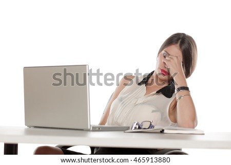 Tired business woman with headache sitting at her desk with a laptop