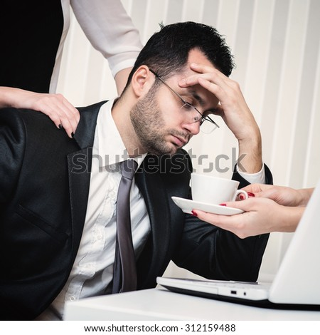 Tired businessman at office. Assistant giving him a massage and other assistant giving him a cup of coffee.  - stock photo