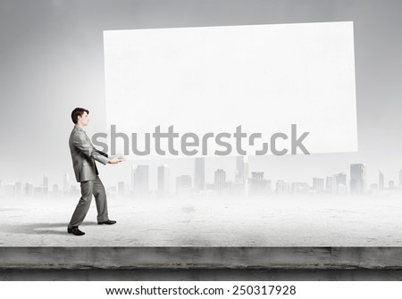 Tired businessman carrying big blank banner. Place for your text - stock photo