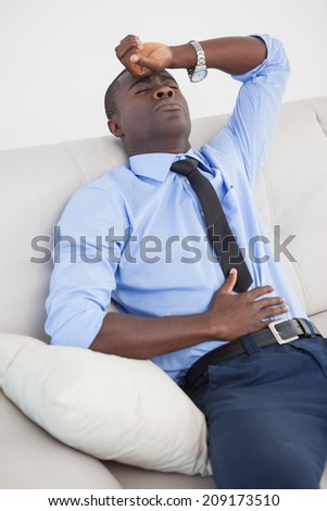 Tired businessman getting a headache at home in the living room - stock photo