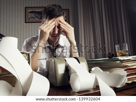 Tired businessman is sitting at a table full of paperwork - stock photo
