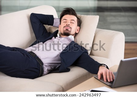 Tired businessman is sleeping on the sofa at the office.