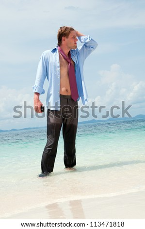 Tired businessman on the beach - stock photo
