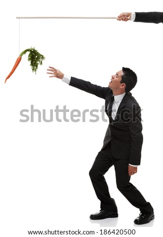 Tired businessman reaching for the carrot on the end of a stick full body - stock photo