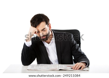 Tired businessman reading newspaper in the office. - stock photo